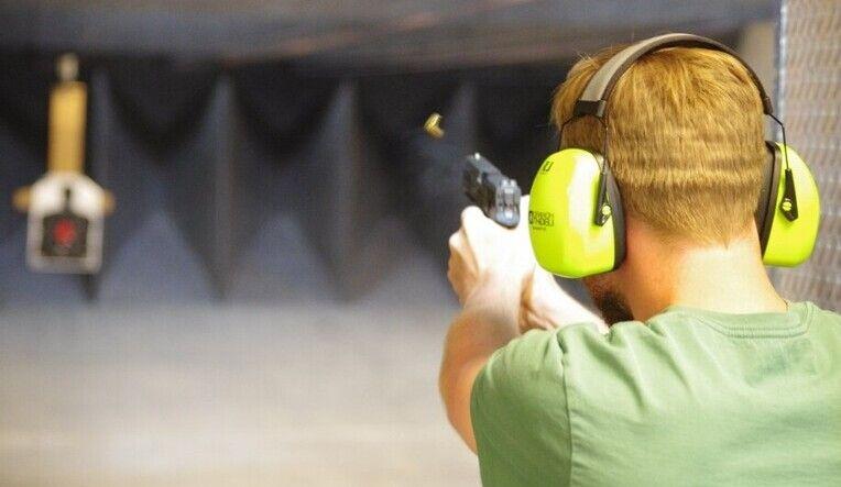 un homme portant un casque anti bruit tir a un stand de tir