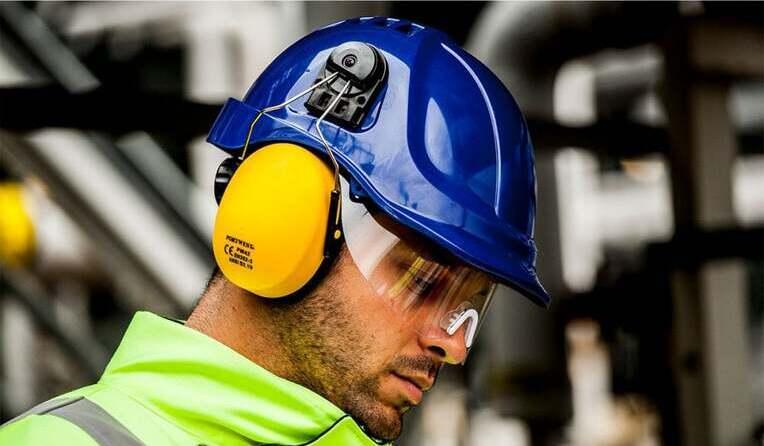 un homme portant des coquilles anti bruit adaptées sur un casque de sécurité