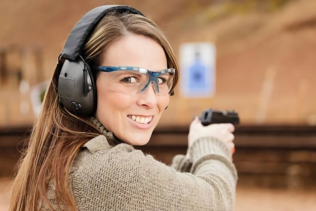 une femme avec un casque anti bruit actif sur un stand de tir