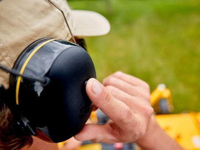 une personne règle le taux de filtration de dB de son casque anti bruit radio